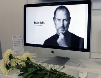 Цветы перед портретом основателя и экс-главы компании Apple Стива Джобса в магазине re:Store. Фото РИА Новости