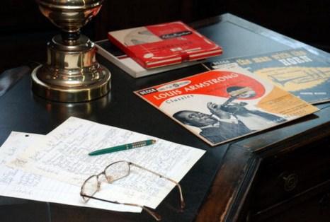 Заметки, сделанные рукой Луи Армстронга, его очки, альбомы и магнитофонные ленты лежат на столе. Фоторепортаж. Фото: STAN HONDA / AFP / Getty Images
