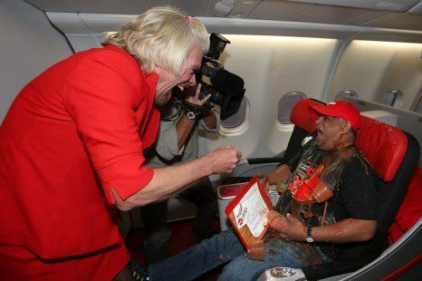 Сэр Ричард Брэнсон отрабатывает проигранное пари на борту бюджетной авиакомпании AirAsia 12 мая 2013 г. Фото: Paul Kane/Getty Images
