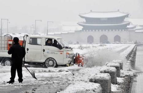 Южнокорейские рабочие удаляют снег напротив главных ворот Дворца в Сеуле. Фото: JUNG YEON-JE