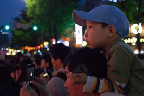 Мальчик смотрит на парад лотосовых фонарей, сидя на плечах у своего отца. Фото: Jarrod Hall/Великая Эпоха (The Epoch Times)