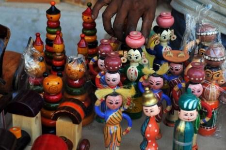 Индийский лавочник поправляет игрушки Channapatna в выставочном зале города Бангалор 12 ноября 2010 года. Эти игрушки представляют собой особую форму деревянных игрушек, которые производятся в городе Channapatna. Это традиционное ремесло отмечено как этнический признак индийской культуры в рамках Всемирной торговой организации в связи с оригинальностью его производственного процесса. Фото: Dibyangshu Саркар / AFP / Getty Images