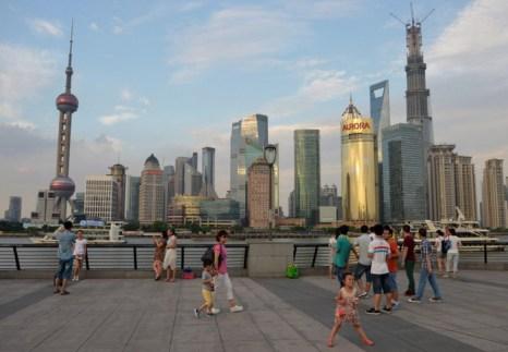 Люди прогуливаются на фоне небоскрёбов Шанхая 3 августа 2013 г. Шанхай — самый большой город Китая по числу жителей, которых насчитывается более 23 миллионов человек. Когда-то о городе говорили как о «рае для авантюристов», но теперь нет почти никаких местных рискованных предприятий, которые стоит так называть. Фото: PETER PARKS/AFP/Getty Images