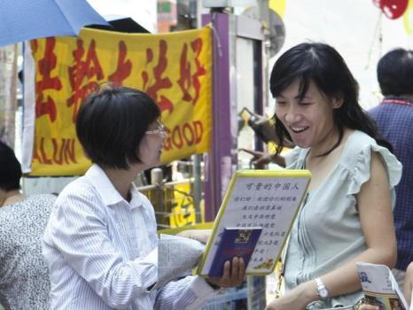 Фото2 — Женщина подписывает заявление о выходе из членов КПК в Гонконге в 2011 г. Фото: Ли Чжэнь/Великая Эпоха (The Epoch Times)
