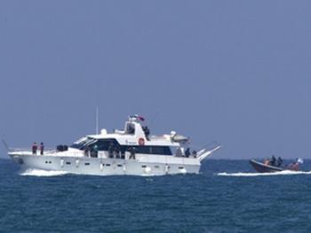 Резиновая лодка военно-морских сил сопровождает яхту каравана