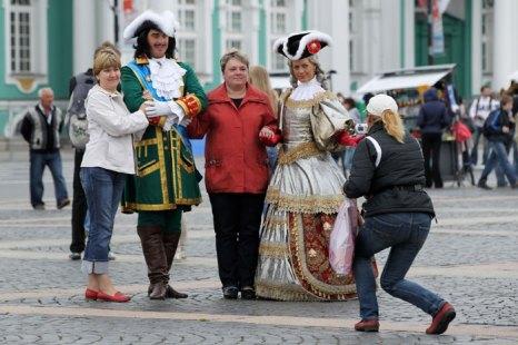 Туристы фотографируются с аниматорами, одетыми в костюмы 18 века напротив Эрмитажа в Санкт-Петербурге, Россия. Фото: Sean Gallup/Getty Images