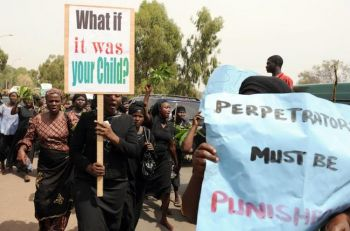 Тысячи женщин в черном, одна из которых несет плакат со словами: «Что, если бы это был ваш ребенок», во время марша в знак протеста против убийства жителей в основном христианской деревни, многие из которых были женщины и дети. Фото: Pius Utomi Ekpei /AFP /Getty Images