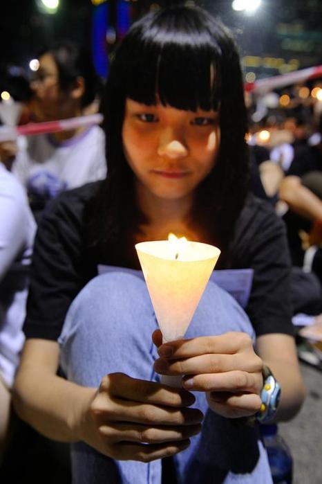 Девушка держит зажжённую свечу в память жертв бойни на Тяньаньмэнь.  Фото: Sung Pi Lung/The Epoch Times