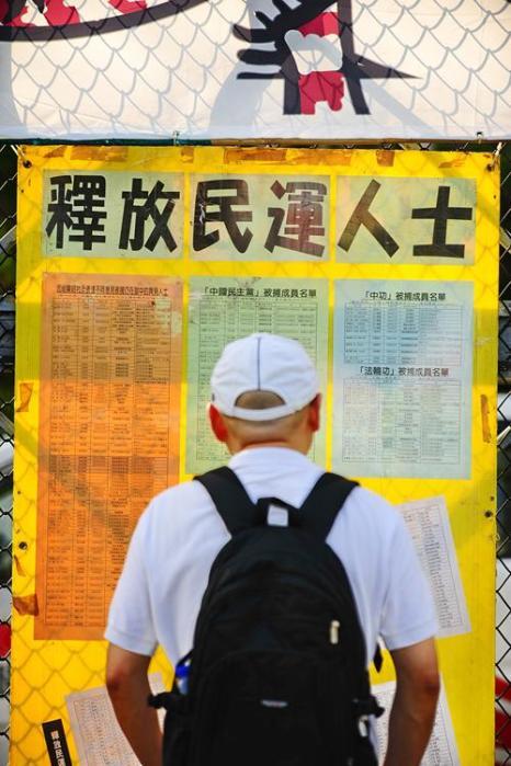 Мужичина стоит перед доской объявлений, где вывешены списки задержанных диссидентов в Китае. В список включены члены различных партий (кроме коммунистической партии Китая), активисты за права человека и последователи Фалуньгун. Фото: Sung Pi Lung/The Epoch Times