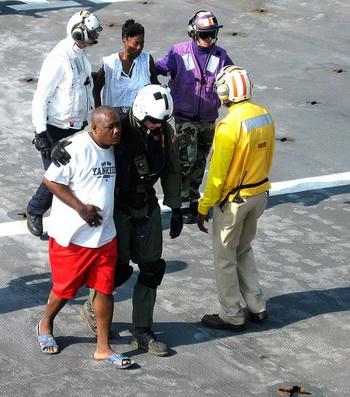 Военные из ВМФ сопровождают пострадавших гаитян на борт корабля НАСА Comfort в больничное отделение. 20 января. Фотос сайта theepochtimes.com