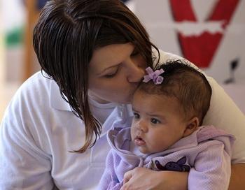 Женщина целует свою трёхмесячную дочь. Фото: Scott Olson / Getty Images