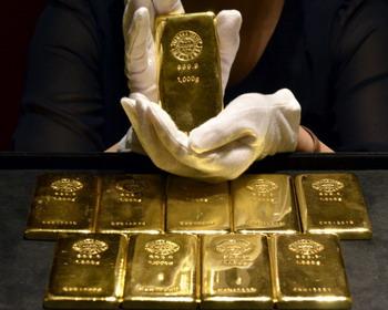 Сотрудник магазина компании Tanaka Kikinzoku в Токио показывает слиток золота весом в 1 кг. Цены на золото в мировых фондовых торгах постоянно повышаются и в августе 2011 года превысили рубеж 1800 долларов за тройскую унцию. Фото:  YOSHIKAZU TSUNO/AFP/Getty Images