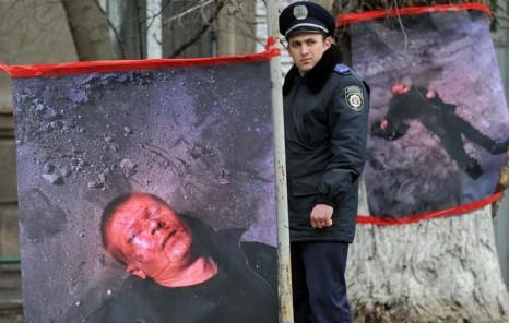 Дорожный полицейский проходит рядом с плакатами, на которых изображён Ростислав Шапошников, руководитель «Дорожного контроля», во время митинга перед зданием Министерства внутренних дел в Киеве 30 марта 2012 года. Фото: SERGEI SUPINSKY/AFP/Getty Images