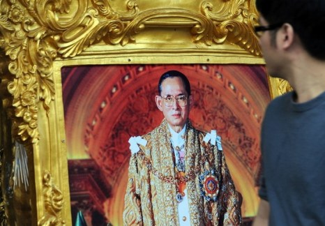 Таец проходит мимо фотографии короля Пумипона Адульядета, продающейся в переулке накануне его дня рождения в Бангкоке 4 декабря 2013. Фото: Indranil Mukherjee/AFP/Getty Images