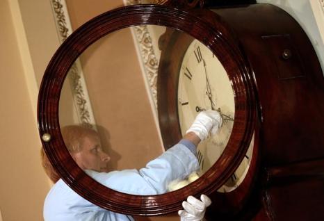 Ричард Доернер, специалист музея Капитолия США, который вернулся сегодня на работу после двухнедельного отпуска, настраивает часы, на следующее утро после принятия законопроекта о возобновлении работы правительства США 17 октября 2013 года. Фото: Win McNamee / Getty Images