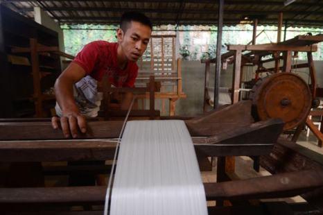 Работник готовит волокна, которые будут использоваться для создания шёлковых тканей на ткацком станке 21 декабря 2013 года в Богоре, Индонезия. Фото: Nurcholis Anhari Lubis/Getty Images