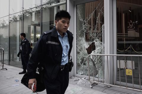Полицейский проходит мимо разбитой стеклянной двери правительственного здания в Адмиралтейском районе Гонконга. 19 ноября 2014 года небольшая группа попыталась ворваться в здание Законодательного совета. Фото: Philippe Lopez/AFP/Getty Images