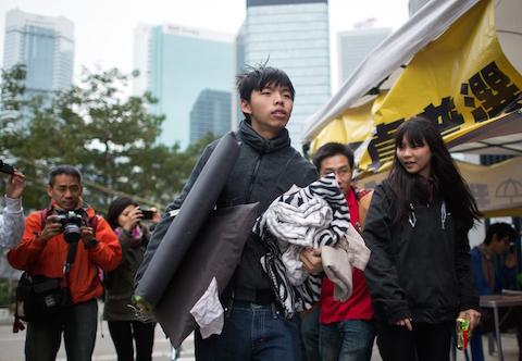 Джошуа Вон (в центре) несёт свои вещи в главном лагере протестного движения в Адмиралтейском районе Гонконга 2 декабря 2014 года. Фото: Johannes Eisele/AFP/Getty Images