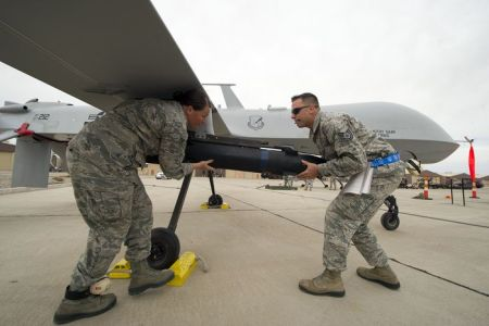 Senior Airman Bethany Lamb and Tech. Sgt. Travis Wheeler load an inert missile onto a MQ-1 Predator during the load crew competition April 5, 2013, at Holloman Air Force Base, N.M. Load-crew competitions are held on a quarterly basis and are used to help build morale through friendly competition. Lamb and Wheeler are 849th Aircraft Maintenance Squadron load crew members. (U.S. Air Force photo/Airman 1st Class Michael Shoemaker)
