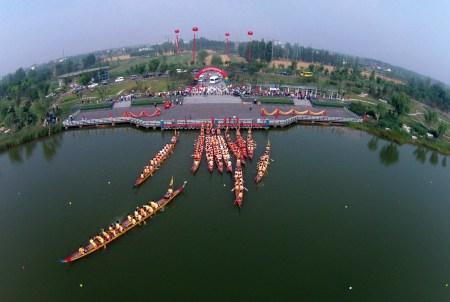 Драконьи лодки отправляются в гонку на реке в городе Биньчжоу провинции Шаньдун 20 июня 2015 года. Гребле на драконьих лодках более 2000 лет, в настоящее время она превратилась в серьёзный спорт. Фото: STR/AFP/Getty Images