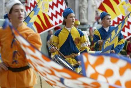 """SIENA, ITALY - AUGUST 15:   Standard bearers of the 'Contrade' (districts) of Palio Siena, dressed in traditional medieval costume during the """"Palio di Siena""""  August 15  2002 in Siena, Italy. The medieval horse race and pageant pays homage to the Madonna and pits the ancient districts of Siena, located about 180 kilometers (112 miles) northwest of Rome, against each other for the victory banner.  (Photo by Franco Origlia/Getty Images)"""