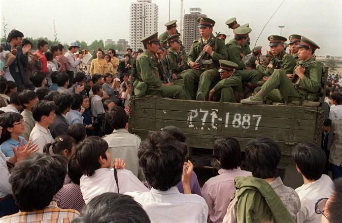 Демонстранты окружили грузовик, в котором едут солдаты НОАК на Тяньаньмэнь, 20 мая 1989 г. Фото: Catherine Henriette/AFP/Getty Images