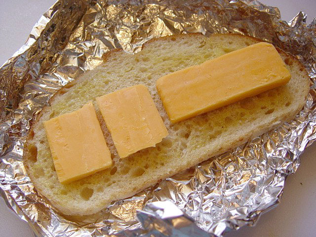 Place the bread on aluminum foil and cheddar slices on the bread