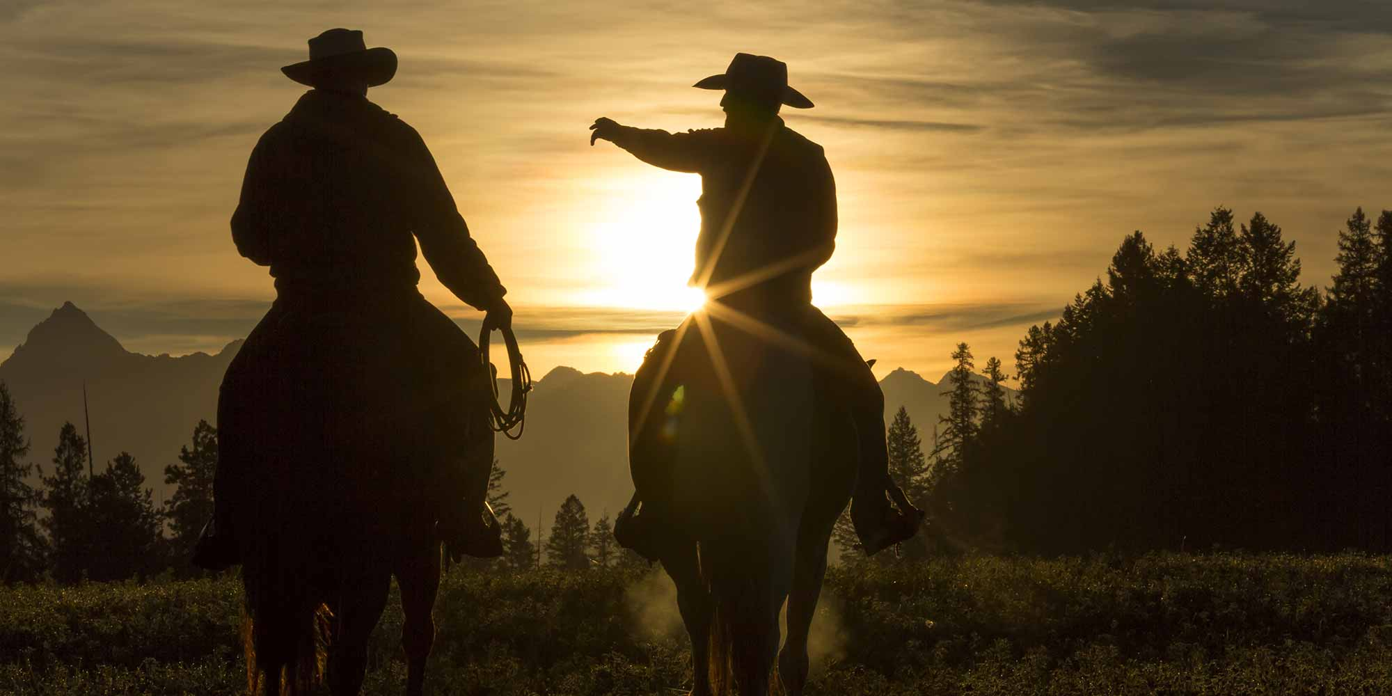 EQ Graphics | Cowboy Silhouettes Riding Horses into The Sunset