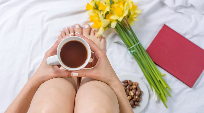 Feng-Shui-Mindfulness-for-the-home--Equate A woman sits on her bed with a cup of coffee, snacks a red book and daffodils.