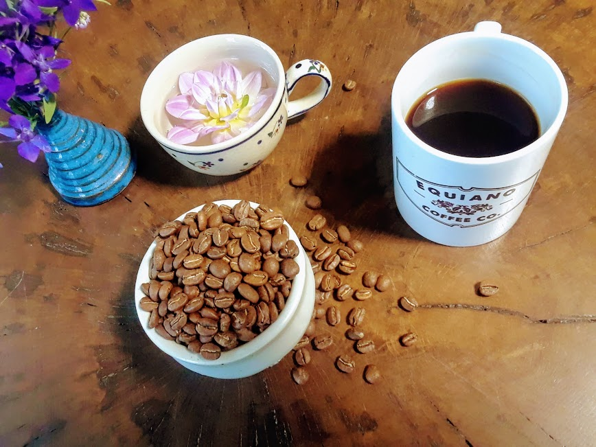 A cup of coffee, flower floating in water, vase of flowers, cup of whole coffee beans.