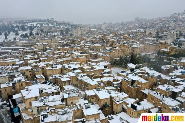 Sebuah gambar yang diambil menggunakan drone menunjukkan rumah dan bangunan diselimuti salju di Hebron, Tepi Barat, wilayah Palestina yang diduduki Israel, Kamis (18/2/2021). Wilayah Palestina diselimuti salju untuk pertama kalinya dalam beberapa tahun.