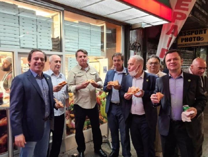 Presiden Brasil Jair Bolsonaro dan rombongannya menikmati pizza di pinggir jalan kota Manhattan, New York karena dilarang masuk ke restoran-restoran. Hal itu disebabkan statusnya yang belum menerima vaksin COVID-19. (Sumber: @GILSONMACHADONETO via REUTERS)