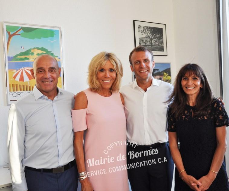 Emmanuel et Brigitte Macron avec Monsieur le Maire de Bormes-les-Mimosas, François Arizzi et son épouse devant l'affiche du Fort de Brégançon par Eric Garence