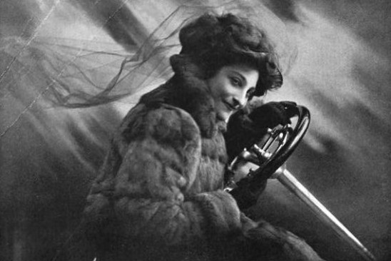 Miss Dorothy Levitt, first British race car driver, comfortably behind the wheel in the early 1900's.