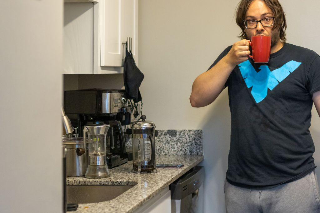eric shay howard drinking coffee red mug