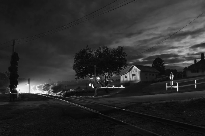 On June 12, 2015, the sun is way over the horizon on a late spring day as NYSW train SU-99 awakens the quite farm at Bairds Lane in Warwick, New York with it's noisy approach.