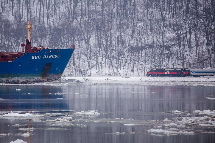 Opposing means of transportation press on through the ice and snow along the Hudson River. The river is a vital artery for both means of transportation.