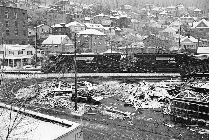 Williamson, WV, February 1994.The train is an important part of this scene, but the inclusion of the lower left building and foreground debris/rubbish help build the story here to show the physical and economic context of the railroad. Photograph by David Kahler and courtesy of the Center for Railroad Photography & Art