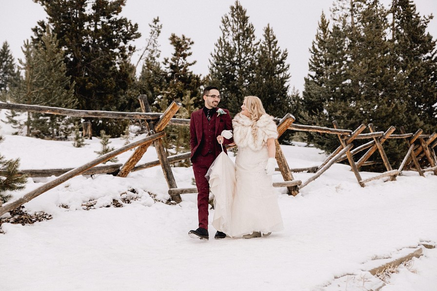 Bride and groom walk down path at Sapphire Point after their snowy elopement