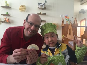 Erikson President and CEO Geoffrey A. Nagle, Ph.D., gets a lesson on making dumplings at an early childhood center in China.