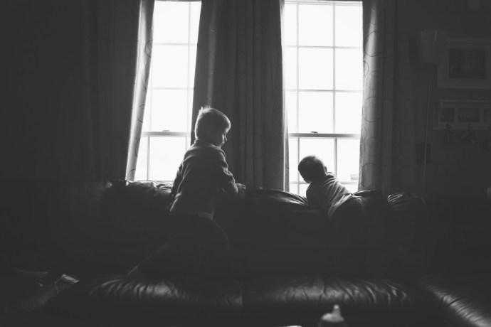 two boys standing on couch