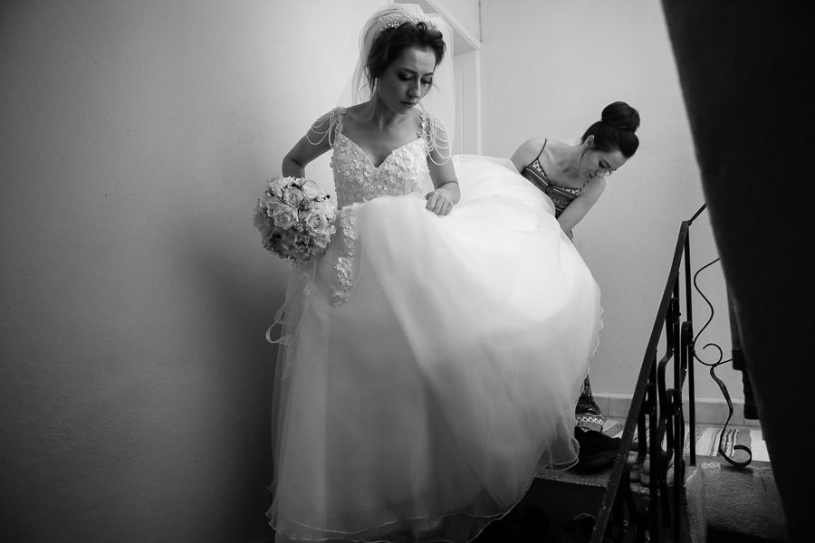 Sister helping bride to get down the stairs