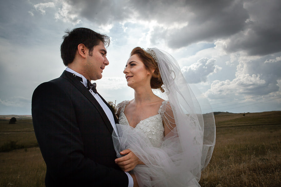 Bride and groom under cloudy sky