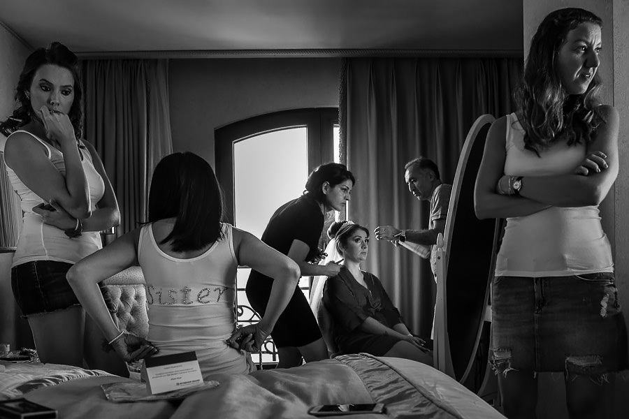 bride getting ready while bridesmaids waiting
