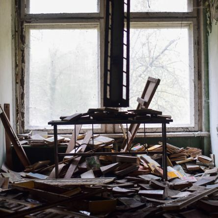 Photo of desk in front of a window surrounded by mess. Photo by Oleksii Hlembotskyi on Unsplash