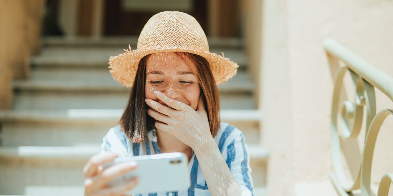 Woman laughing while looking at something on her phone.