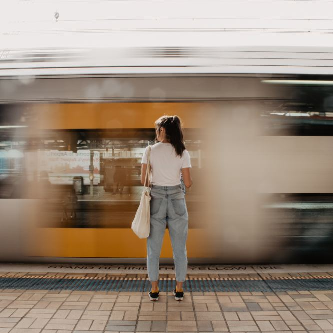 Young woman with brown hair in a pony tail stands on an outdoor subway platform in daylight, while a blurry train speeds past.