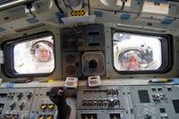 Astronautas mirar a través de la popa de Shuttle ventanas de la cabina de vuelo