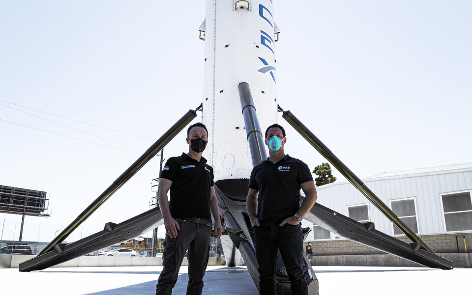 ESA astronauts Matthias Maurer and Thomas Pesquet stand in front of a SpaceX rocket