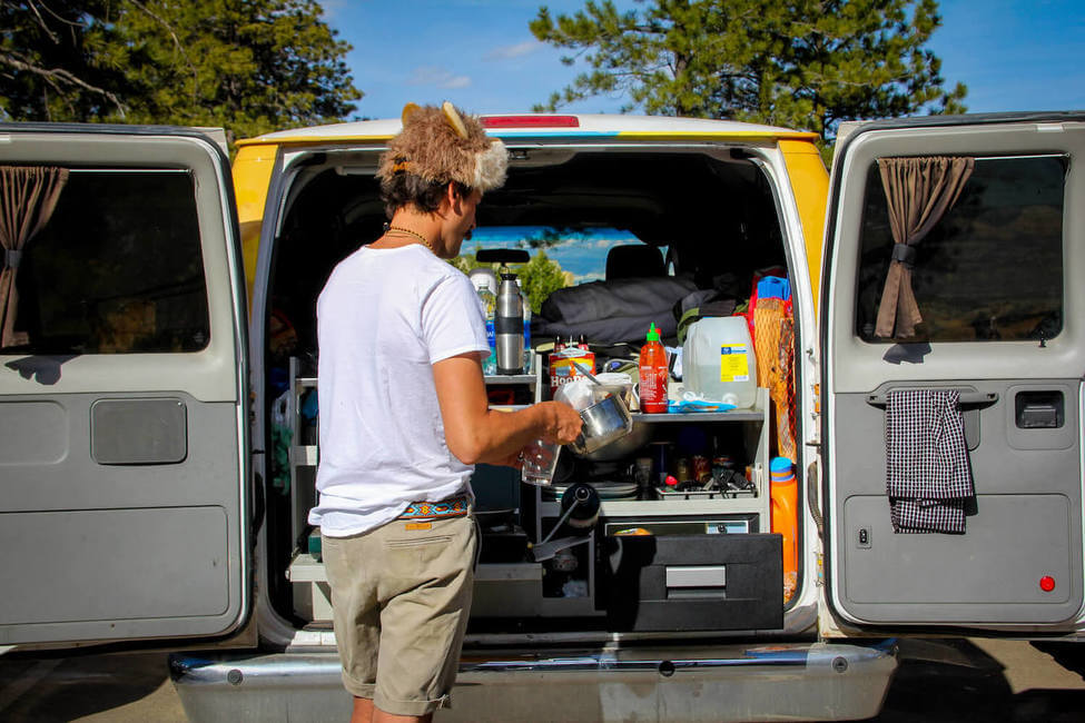 A young man cooking in a campervan kitchen